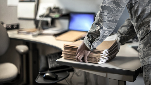 Man in camo picking up stack of files